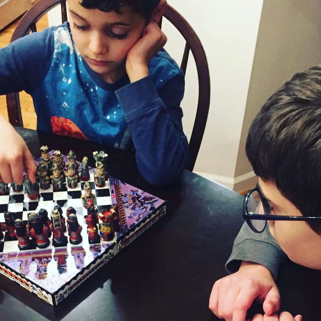 Kids activities playing chess www.thethreeyearexperiment.com